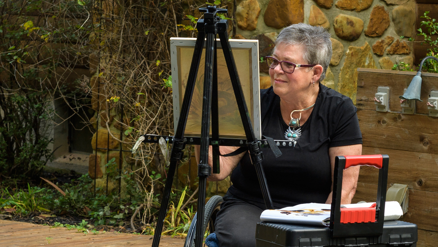 UD Osher Lifelong Learning Institute member paints at easel.