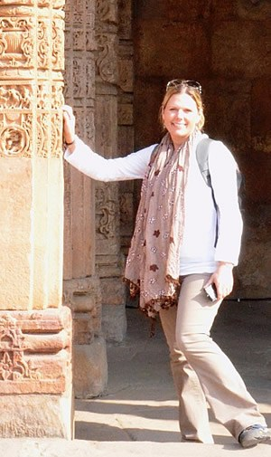 Karen Gates, RN Refresher online program graduate leaning on ornately decorated stone columns.