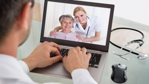 man looking at woman and nurse on laptop screen