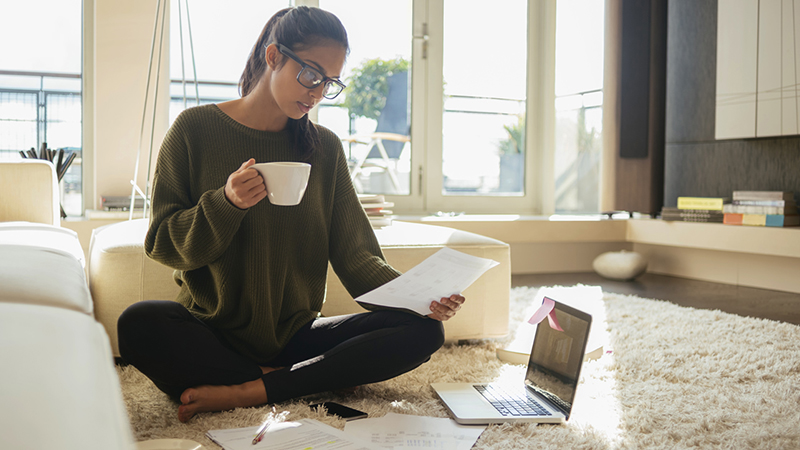 woman sitting on floor with laptop drinking coffee with legs crossed