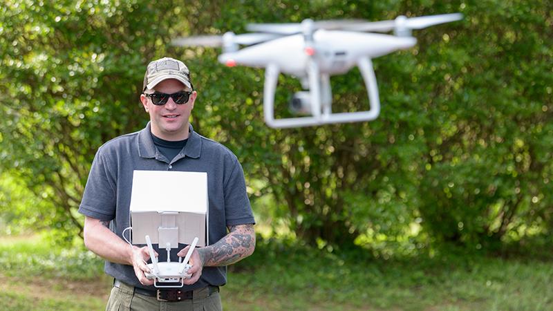 student Tavis Miller flying drone in a park