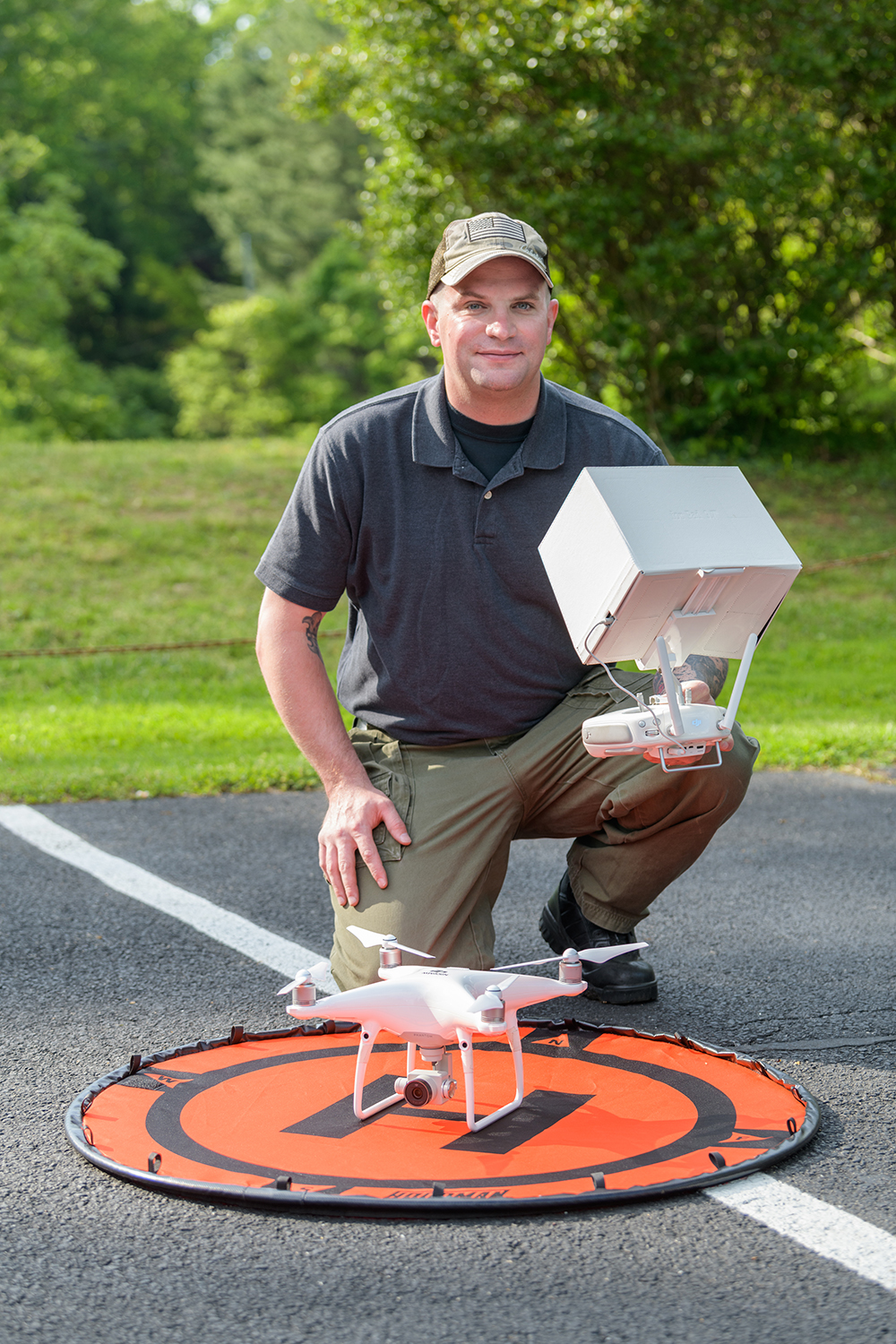 Tavis Miller kneeling over a target with a drone in the center