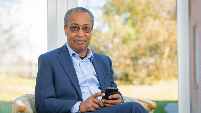 Tony Powell looking forward with smartphone in hand and trees behind window in background