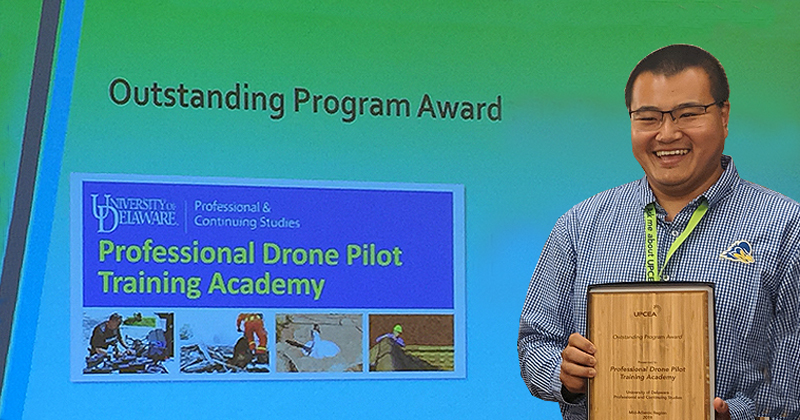 Vic Wang poses with 2019 UPCEA Mid-Atlantic Region Outstanding Program Award plaque for the UD PCS Professional Drone Pilot Training Academy