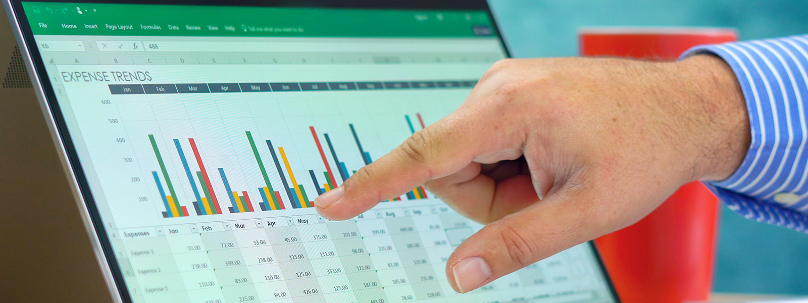 Hand pointing at Microsoft Excel bar chart on tablet