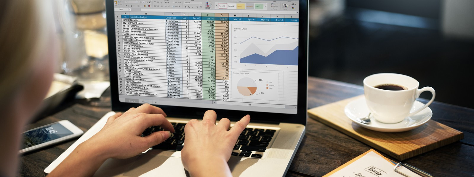 Two hands on laptop with Excel table on screen and cup of coffee to the right