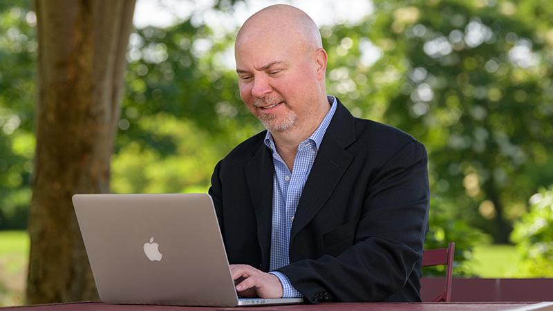 Tom Nesterak working outside on a laptop