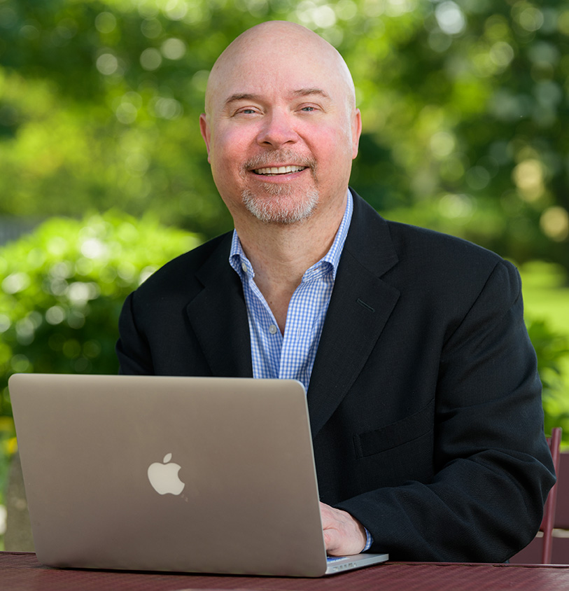 Tom Nesterak on laptop outdoors