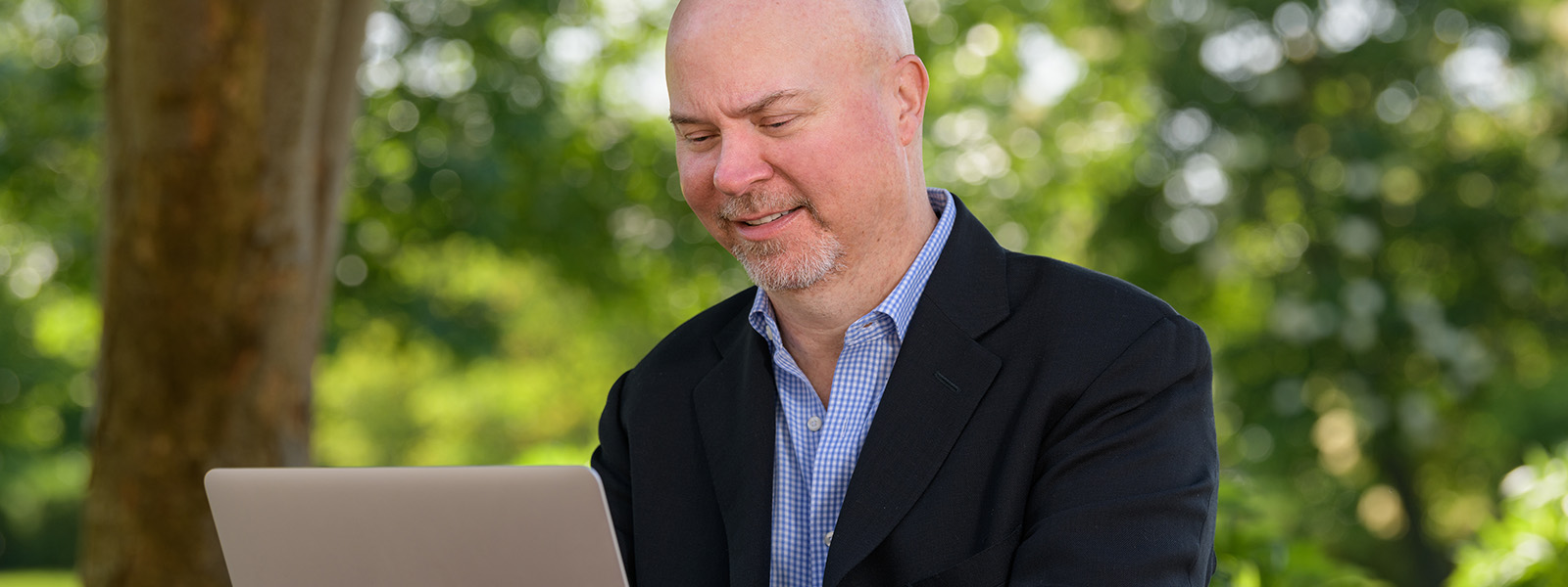 Tom Nesterak on laptop outdoors