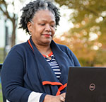 Thonnia Lee on laptop outdoors