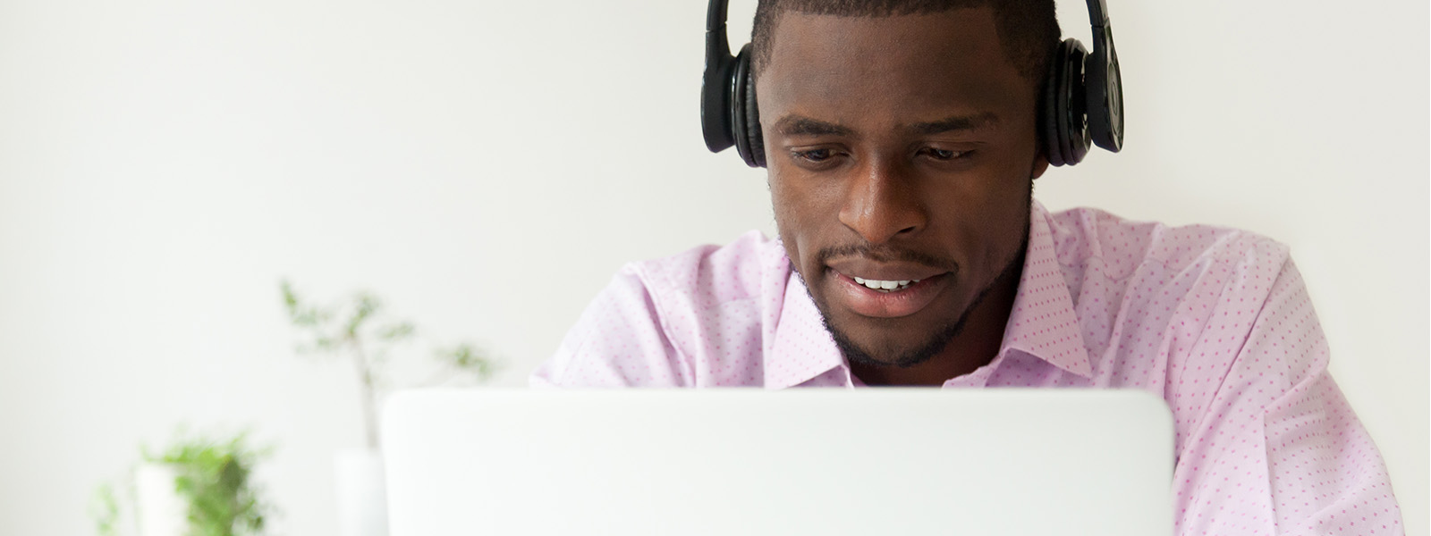 A middle-aged man with headphones working on a laptop.