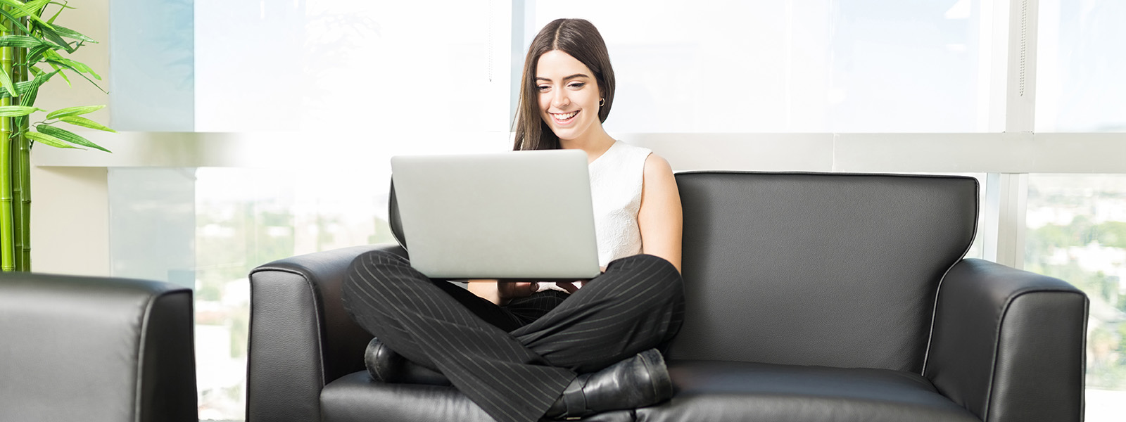 Smiling woman with legs crossed sitting on couch working on laptop