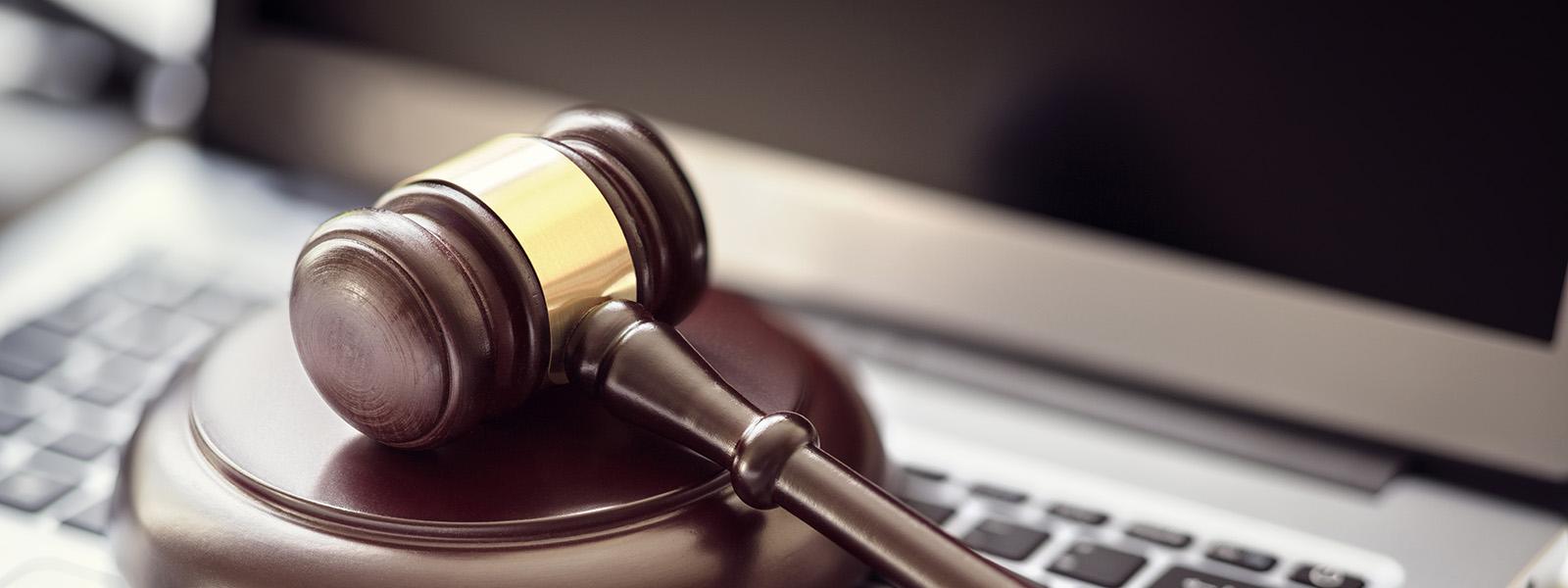 lawyer gavel on top of laptop keyboard
