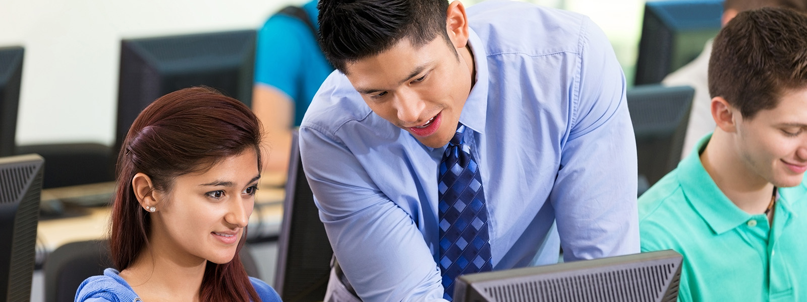 Male teacher standing and pointing at computer screen female student is sitting in front of
