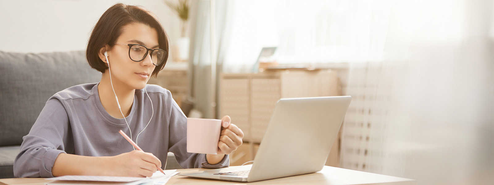 woman sitting on floor working on laptop with pen in right hand and mug in left hand