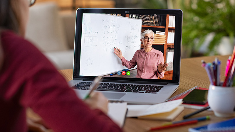 Laptop screen with female teacher pointing at whiteboard