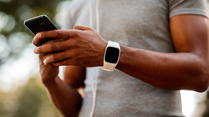 male athlete wearing fitness tracker on left wrist using smartphone with both hands
