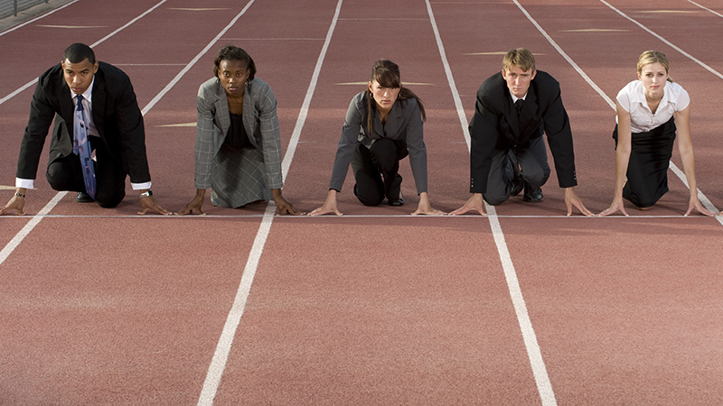 Five adults in business attire ready to run a race on a track