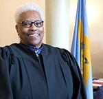 Paralegal graduate Carmen Jordan Cox in magistrate gown in front of Delaware flag