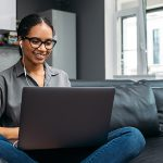 Woman at home sitting on couch working on laptop