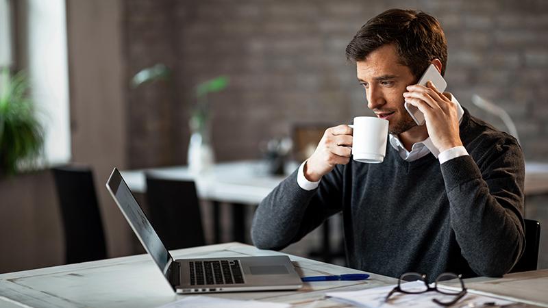 Man talking on phone, drinking coffee, looking at laptop screen