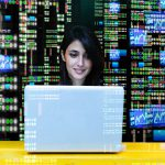Woman on laptop with wall of data behind her