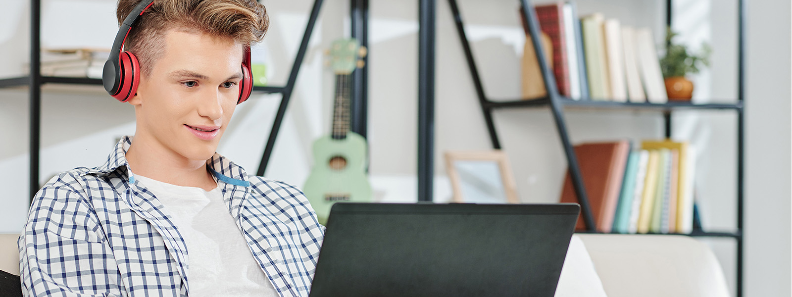 Teenage boy on couch wearing headphones working on laptop